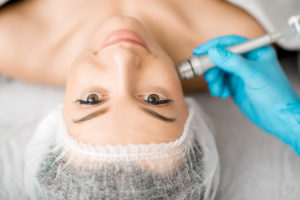 Young woman during the facial treatment procedure in the cosmetology office