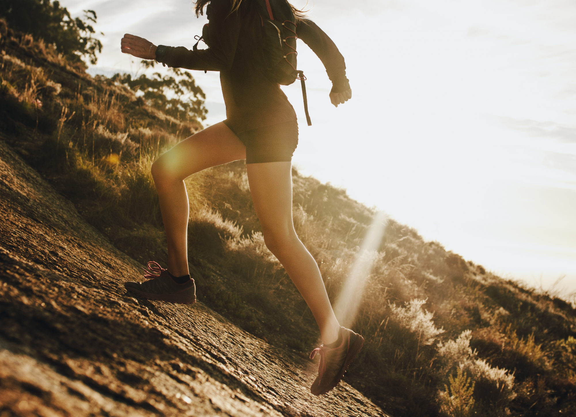 Woman running up a rocky mountain slope. Cropped shot of female trail runner running uphill on a sunny day.